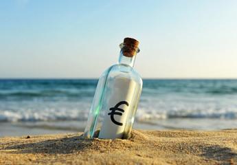 Botella con el símbolo del euro en la orilla de la playa