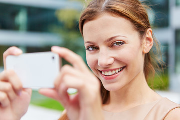 Smiling woman taking pictures with smartphone