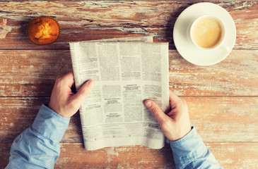 close up of male hands with newspaper and coffee