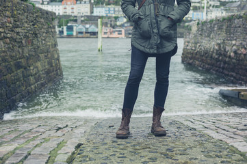 Feet and legs of person by water in harbour