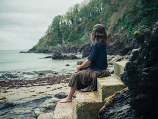 Young woman relaxing on stairs in nature by sea