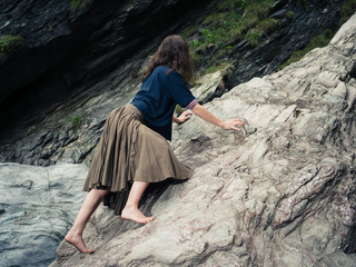 Young barefoot woman climbing rocks