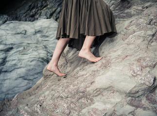 Barefoot woman climbing rock