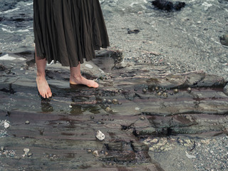 Feet of young woman walking on rocks in water