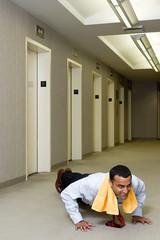 Office worker doing push ups in corridor