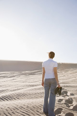 Woman in desert holding shoes