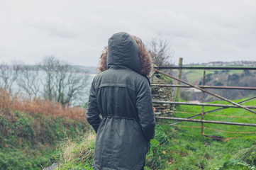 Person wearing winter coat by gate in countryside