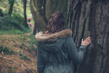 Young woman in winter coat by tree