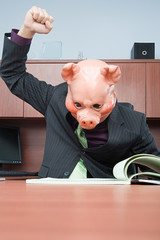 Businessman in pig mask reading