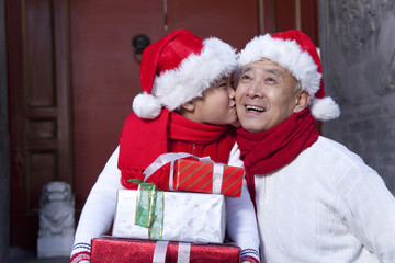 Grandpa and grandson holding Christmas Gifts
