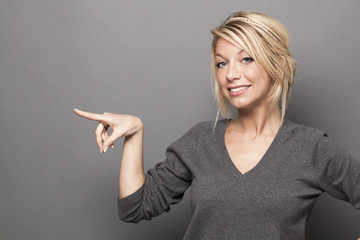 body language concept - gorgeous 20s blond woman pointing at an advertisement with her finger,studio shot on gray background