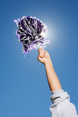 Arm of a cheerleader holding pom-pom