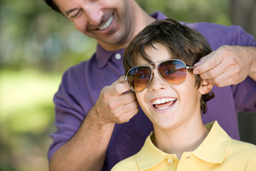 Father putting sunglasses on son