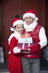 Young couple holding Christmas Gifts