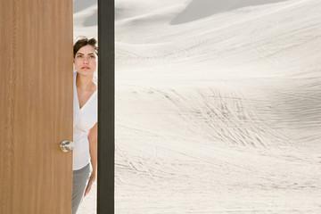 Woman opening door in desert
