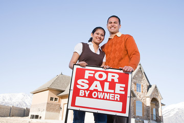 Portrait of a couple hold a for sale sign