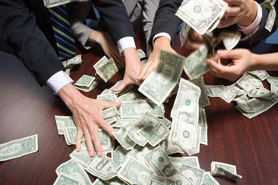 Businesspeople grabbing money