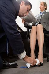Man polishing businesswoman's shoes