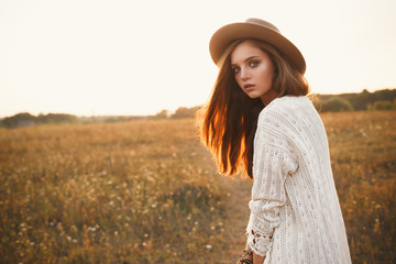 Fashion portrait of beautiful young pretty girl with hippie outfit and hat outdoors at sunset. Soft warm color tone. Boho lifestyle. Bohemian Style. Horizontal with blank space for text