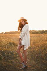 Fashion portrait of beautiful skinny and pretty girl with hippie outfit and hat standing in the field at sunset. Soft warm color tone. Boho lifestyle. Bohemian Style. Vertical with space for text