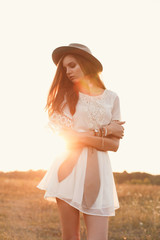 Fashion portrait of beautiful young pretty girl with hippie outfit and hat standing in the field at sunset. Soft warm color tone. Boho lifestyle. Bohemian Style. Vertical with blank space for text