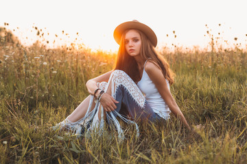 Fashion portrait of beautiful young pretty girl with hippie outfit and hat outdoors in the field at sunset. Soft warm color tone. Boho lifestyle. Bohemian Style. Horizontal with blank space for text