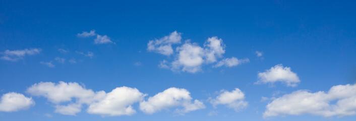 Cloudscape over horizon. White heap clouds in the blue sky.