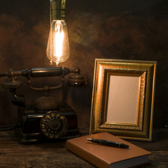 Still life of vintage telephone with picture frame and diary on