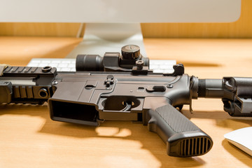 Army carbine on a wooden computer table in office room,Worm tone image
