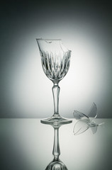 Broken crystal  glass with reflection on white illuminated backg