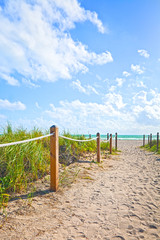 Path of sand going to the beach and ocean in Miami Beach Florida , on a beautiful summer morning with blue sky