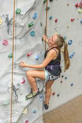 sportliche junge Frau an der Kletterwand