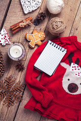 Christmas set. Warm blanket, sweater with a deer, candle, notebook, spices, cinnamon, pine cones, heart  on the wooden background