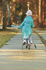 Girl in blue cloak rides bicycle