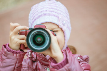 little girl in with red camera photographs