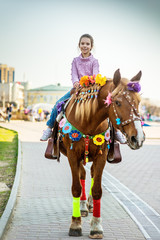 Little girl riding festive horse