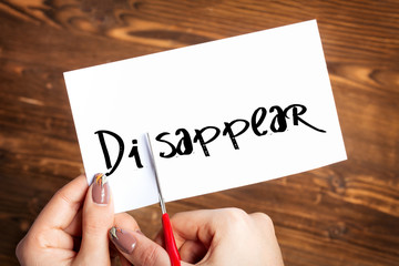 Woman hands cutting card with the word disappear