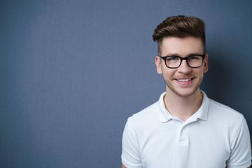 sympathischer junger mann mit brille lächelt in die kamera