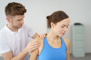 therpeut behandelt die schmerzende schulter einer patientin