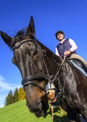stolzes Pferd mit gutgelaunter Reiterin
