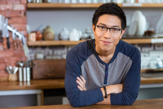 Confident handsome man standing in cafe with arms crossed