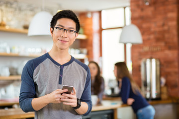 Handsome asian man standing in cafe and using mobile phone