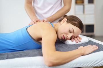 therapeut untersucht eine junge frau mit schmerzen an der schulter