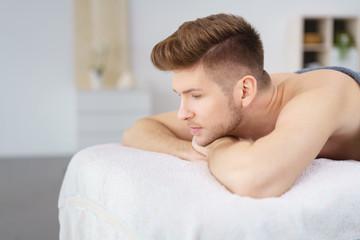 mann liegt auf massageliege und wartet auf die behandlung