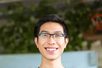 Asian positive cheerful young man in glasses