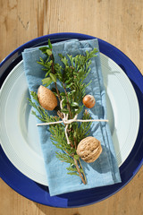 Folded blue napkin decorated with evergreen plants, nuts and twine