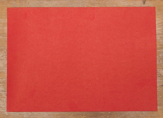 Red paper on wooden background