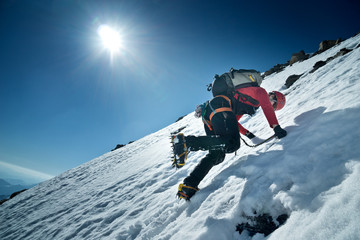 Fotobehang Alpinisme Bergsteiger klettert die Nordwand des Fuscherkarkopf, Österreich. Kletterer schlägt mit den Steigeisen Stufen ins Eis.