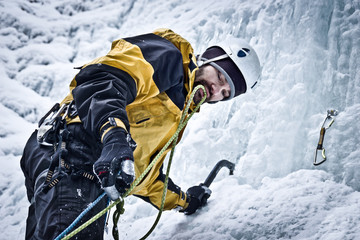 Bergsteiger klettert mit Eisgeräten einen gefrorenen Wasserfall hinauf. Eiskletterer richtet eine Sicherung ein.