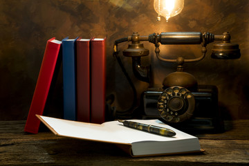 Still life of vintage telephone on table with diary book